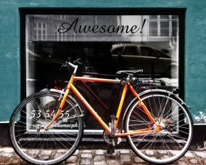 Awesome orange vintage bike in front of window leaning up against wall. Stock Photography Free for Commercial Use.