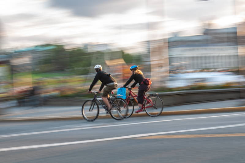 Couple of cyclists in urban setting riding bicycles through streets with speed blur. Stock Photography Free for Commercial Use.