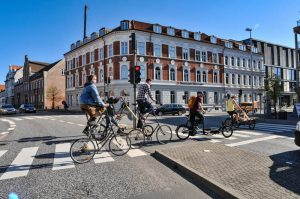 Group of cyclists in Denmark riding vintage bicycles through crosswalk. Stock Photography Free for Commercial Use.