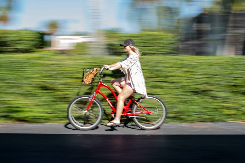 Woman Biking on sidewalk in front of green bushes with speed blur. Stock Photography Free for Commercial Use.