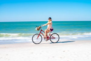 Woman Biking on tropical sand in front of waves. Stock Photography Free for Commercial Use.