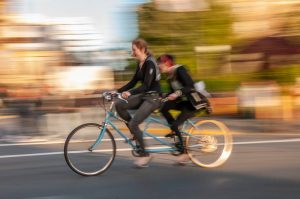 Two women on tandem bike in the fall, speed blur. Stock Photography Free for Commercial Use.