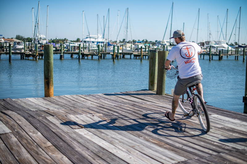 Image of biker on wooden dock overlooking the ocean and sailboats. Stock Photography Free for Commercial Use.