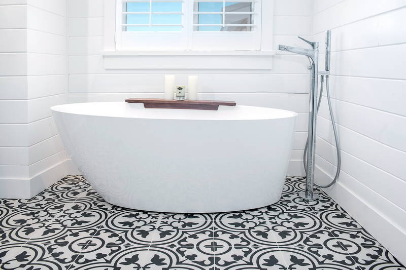 Beautiful white tub on patterned tile in bathroom with shower. Stock Photography Free for Commercial Use.
