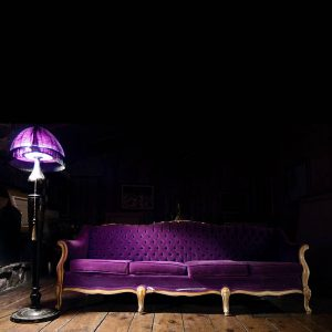 Purple couch under purple lamp with wooden hardwood floor, vintage retro velvet fabric couch. Stock Photography Free for Commercial Use.