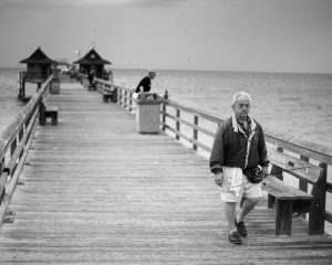 Long pier in black in white, old man walking, beautiful ocean. Stock Photography Free for Commercial Use.