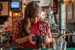 Woman in pub using digital camera, adjusting settings on DSLR. Stock Photography Free for Commercial Use.