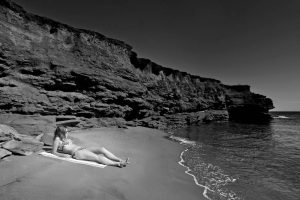 Beautiful woman on beach underneath cliff in bikini. Stock Photography Free for Commercial Use.