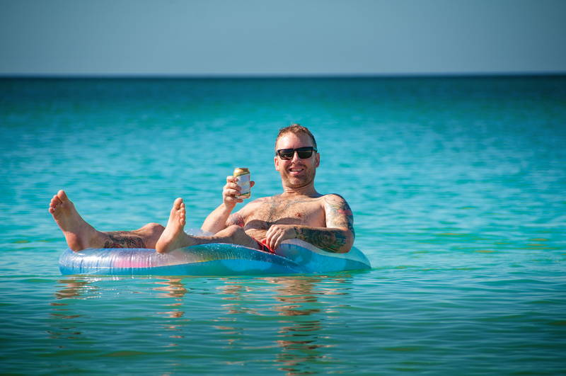 Man in inner-tube on all-inclusive vacation in clear Caribbean water. Stock Photography Free for Commercial Use.
