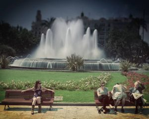 People on bench in front of lawn and waterfall. Stock Photography Free for Commercial Use.