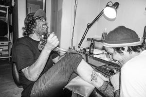 Tattoo artist in small studio, black and white with punk rock men laughing. Stock Photography Free for Commercial Use.
