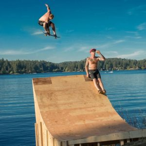 Skateboard ramp with rider launching into lake. Stock Photography Free for Commercial Use.